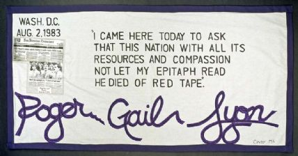 White AIDS panel quilt with purple border, big purple lettering and small black lettering
