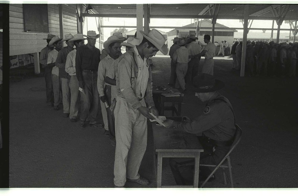 black and white image of many people waiting in line