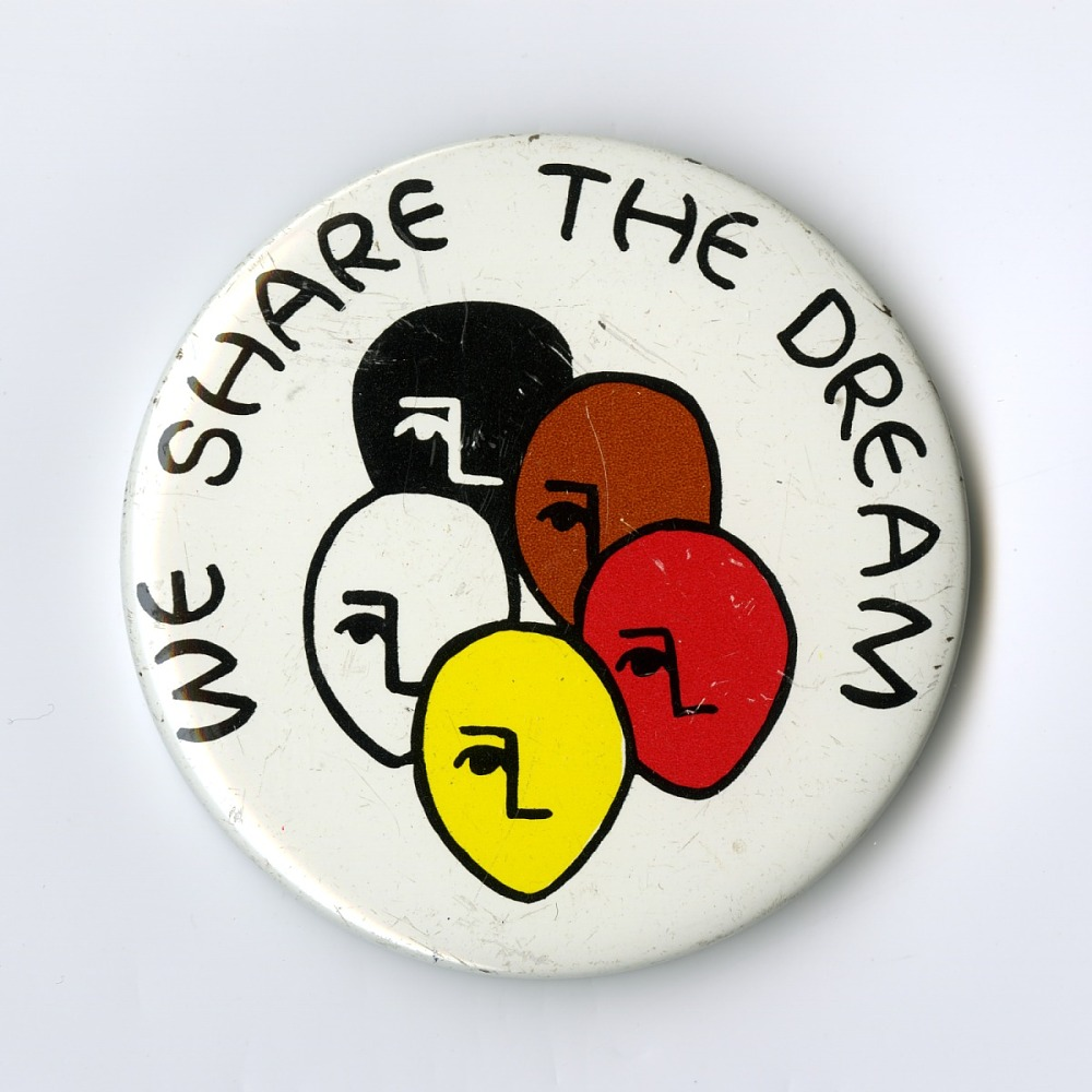 "button with red, white, black, brown, yellow faces with words ""We Share the Dream"""