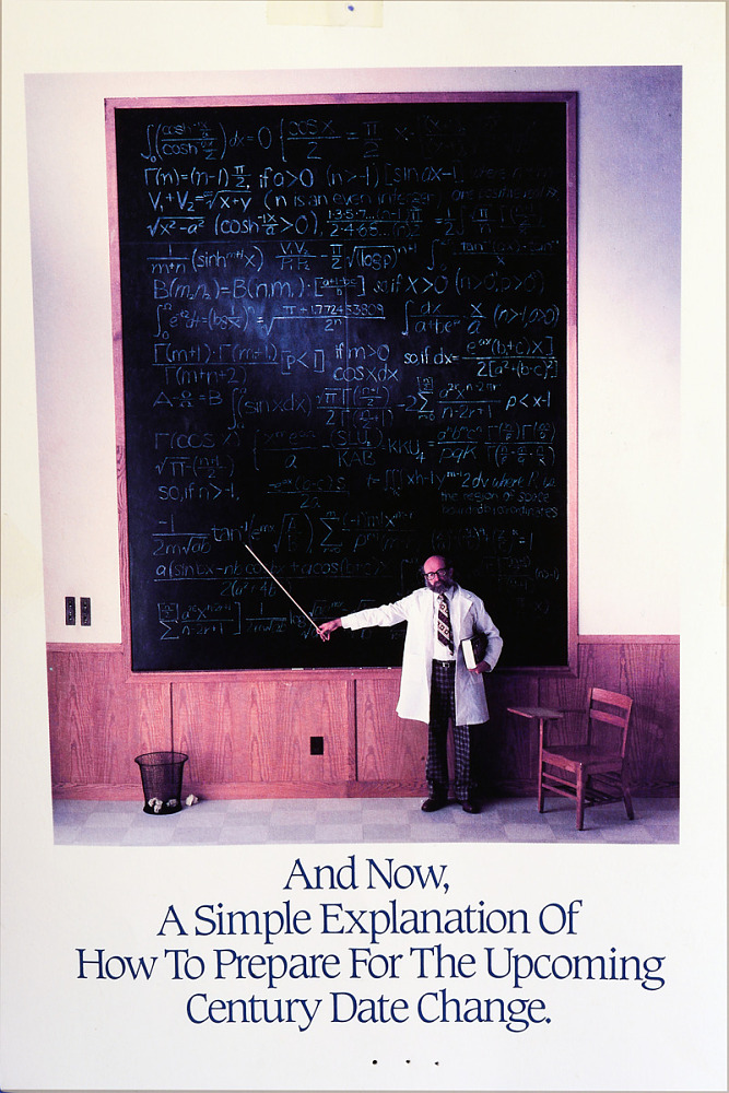 An image of a man standing in front of a very large chalkboard, holding a pointer
