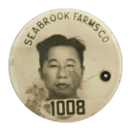 "White button with picture of a Japanese American with the words ""SEABROOK FARMS CO"" along the top and the number 1008 along the bottom"