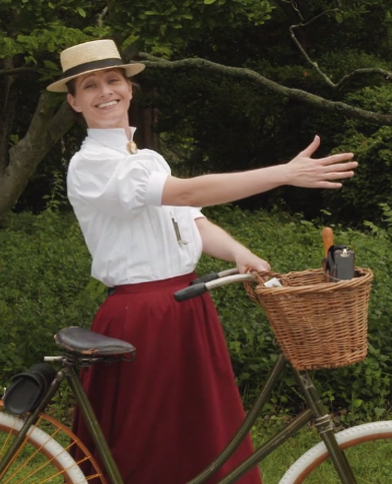 Image of the Wheelwoman standing by her bicycle