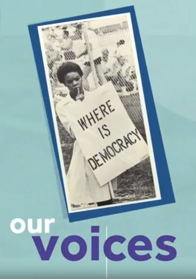 "Screenshot from What Will You Stand For? video, with blue background, image of young woman holding a sign that says ""Where is Democracy"" and the text ""our voices""."