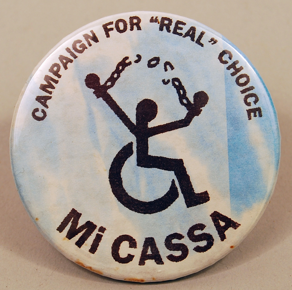 """Pin-back button with symbol of a person in a wheelchair breaking chains, with the words """"Campaign for """"Real"""" Choice"""" and """"Mi Cassa"""" on the top and bottom of the pin, respectively."""