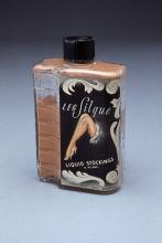 Image of a bottle of white leg paint with picture of a woman's leg on a black label