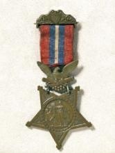 Brass colored medal with red, blue and white ribbon