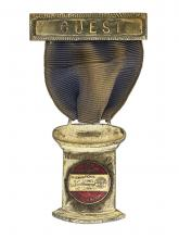 "Medallion badge with the word ""GUEST"" written at top"