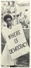 "Woman holding a sign that reads ""Where is Democracy?"""