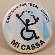 "Pin-back button with symbol of a person in a wheelchair breaking chains, with the words ""Campaign for ""Real"" Choice"" and ""Mi Cassa"" on the top and bottom of the pin, respectively."