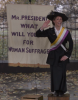 Image of the suffragist standing on a soapbox and in front of a banner, delivering an open-air speech